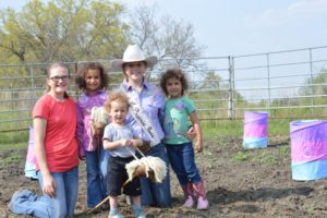 rodeo queen with kids and stickhorses